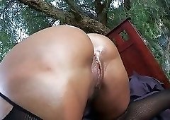 Fishnets-wearing brunette with a bodysuit gets fucked on a bed outdoors