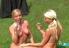 Two busty lesbians are toying anal holes on the lawn in broad daylight