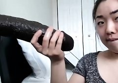 Naughty Asian camgirl with nice tits sucks a huge black toy