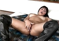 Boots-wearing brunette fingering her pussy for you