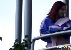 This redhead loves showing off her private parts on the balcony